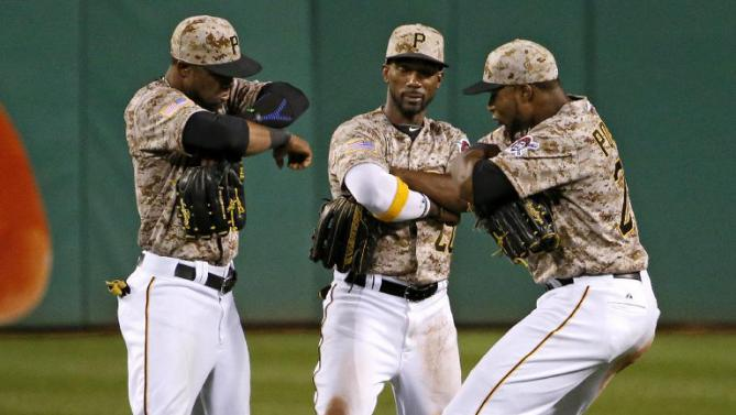 Pittsburgh Pirates left fielder Starling Marte, left, center fielder Andrew McCutchen, and right fielder Gregory Polanco celebrate a 7-2 win over the Cincinnati Reds in a baseball game Thursday, May 7, 2015, in Pittsburgh. (AP Photo/Gene J. Puskar)